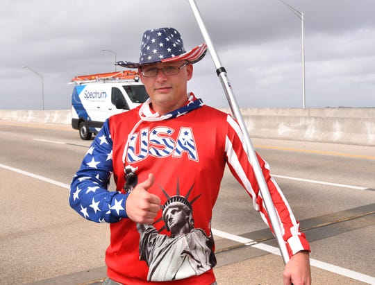 Indialantic Trump supporter Robert Walker marchedthe Melbourne Causeway alongside the Parkland procession, carrying a long metal pole bearing four pro-Trump flags.