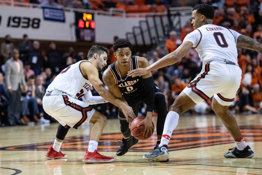 Feb 15, 2020; Stillwater, Oklahoma, USA; Oklahoma State Cowboys guard Avery Anderson III (0) and Texas Tech Red Raiders guard Davide Moretti (25) /fight for a loose ball during the first half at Gallagher-Iba Arena. Mandatory Credit: Rob Ferguson-USA TODAY Sports