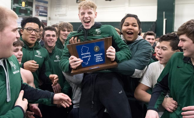 Members of the West Deptford High School wrestling team celebrate with their trophy after West Deptford defeated Haddonfield, 39-21, in the South Jersey Group 2 wrestling final held at West Deptford High School on Friday, February 14, 2020.