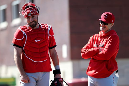 Cincinnati Reds catcher Curt Casali (12), left, and Cincinnati Reds manager David Bell (25), right, share a laugh, Saturday, Feb. 15, 2020, at the Cincinnati Reds Spring Training Facility in Goodyear, Arizona.