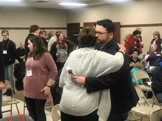 Troy Price receives a hug before the start of a meeting by the Iowa Democratic Party. Price resigned his post earlier in the week after a reporting app failed during the Iowa caucus, and results took weeks to determine. The party met at Machinist Hall in Des Moines, Saturday, Feb. 15, 2010.