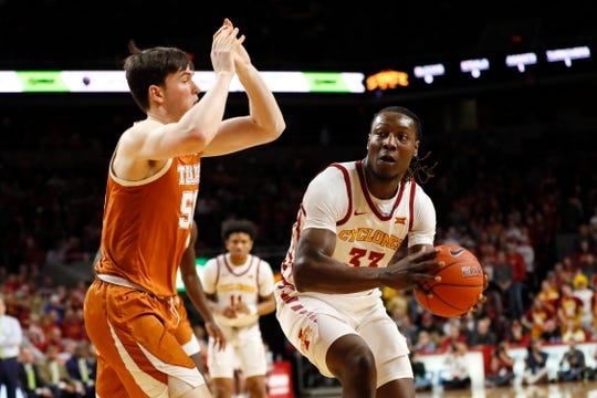 Iowa State forward Solomon Young drives to the basket past Texas center Will Baker, left, during the first half of an NCAA college basketball game, Saturday, Feb. 15, 2020, in Ames, Iowa.