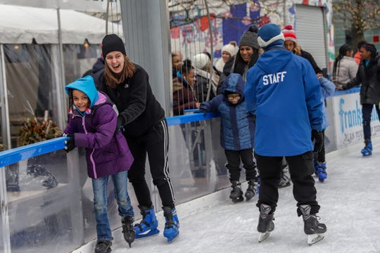 Kendasia Spears, 7, and her mother Alisha Spears, 29, step onto the ice at Campus Martius with other families during the Angel Tree Sports Clinic organized by Prison Fellowship in downtown Detroit on Saturday.