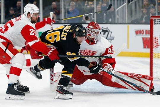 Boston Bruins' David Krejci chases the puck after his shot was blocked by Detroit Red Wings goalie Jonathan Bernier during the second period in Boston, Saturday, Feb. 15, 2020.
