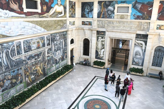 Visitors look at industry murals by artist Diego Rivera at the Detroit Institute of Arts.