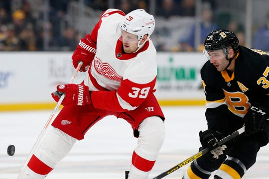 Boston Bruins' Patrice Bergeron (37) and Detroit Red Wings' Anthony Mantha (39) battle for the puck during the third period.