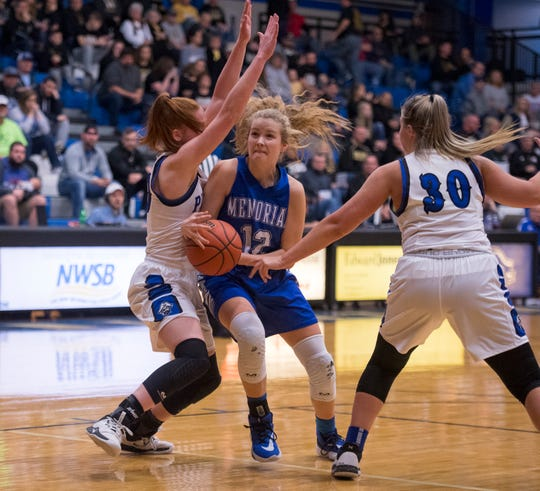 Memorial's Peyton Murphy (12) feels pressure from Greensburg Lady Pirates defense during the IHSAA Class 3A girls basketball regional at Charlestown High School in Charlestown, Ind., Saturday morning, Feb. 15, 2020.