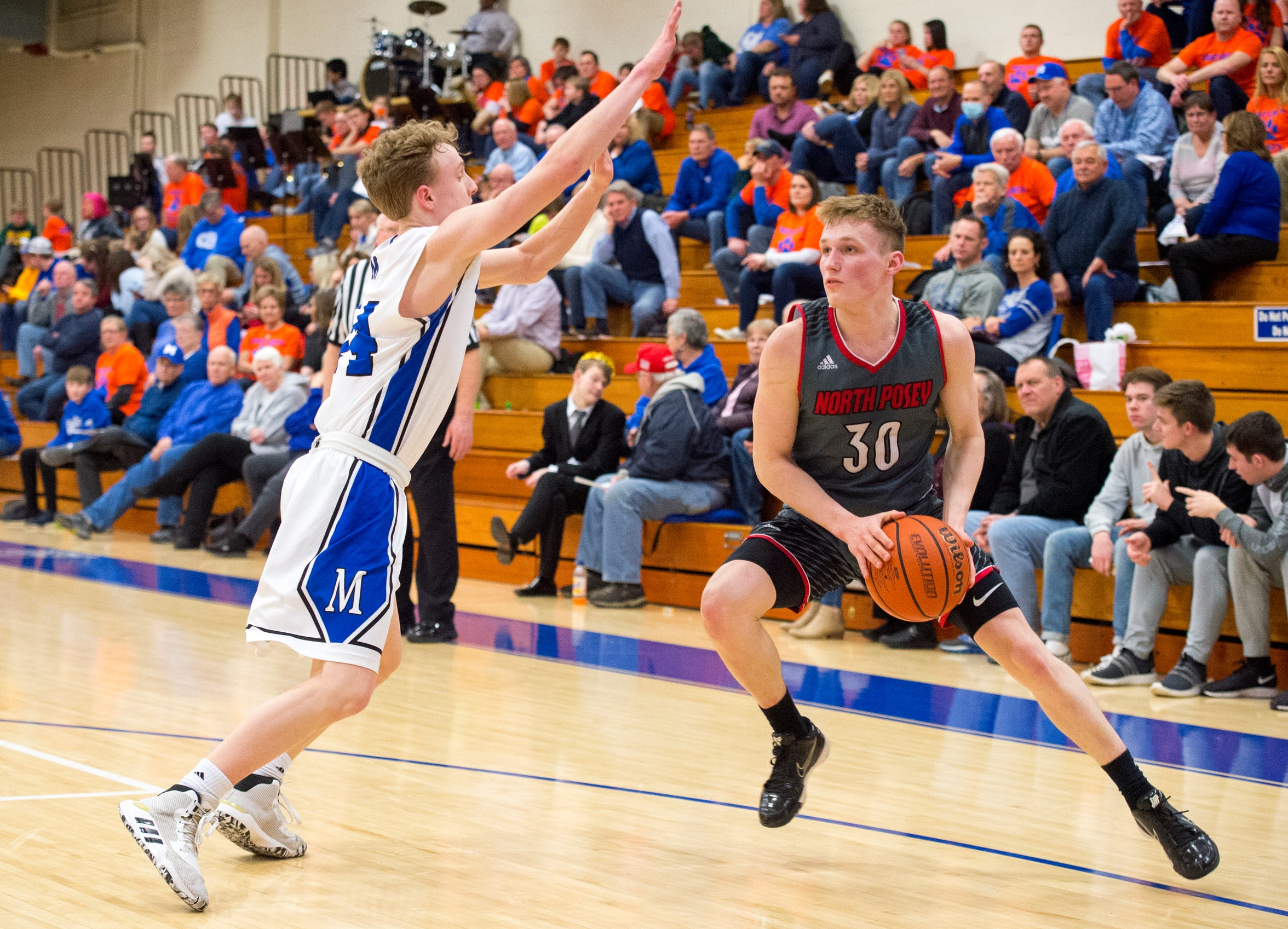North Posey's Josiah Ricketts (30) steps back guarded by Memorial's Andrew Helmerich (14) as the North Posey Vikings play the Memorial Tigers play at Robert M Kent Athletic Center in Evansville, Ind., Friday night, Feb. 14, 2020.