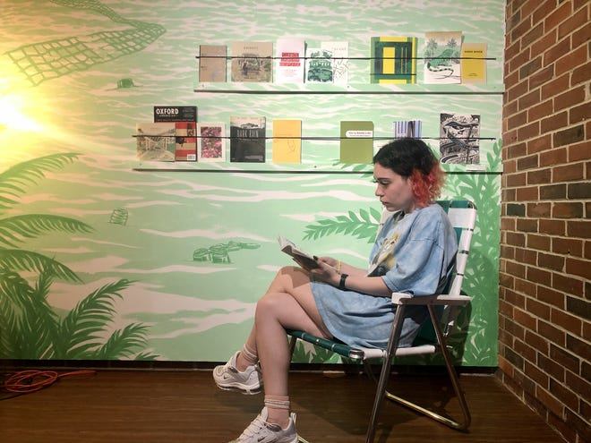 Casey Riguerra sitting and reading a zine on display at the Museum of Fine Arts.