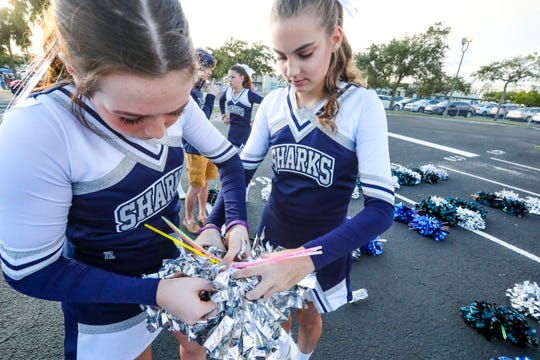 Oasis cheerleaders Danielle Zaccaria and Kayla Hoagland add glow sticks to their pompoms. Parade participants met at Fort Myers High School to line up for the  Edison Festival of Light Grand  Parade on Saturday, Feb 15. 2020.