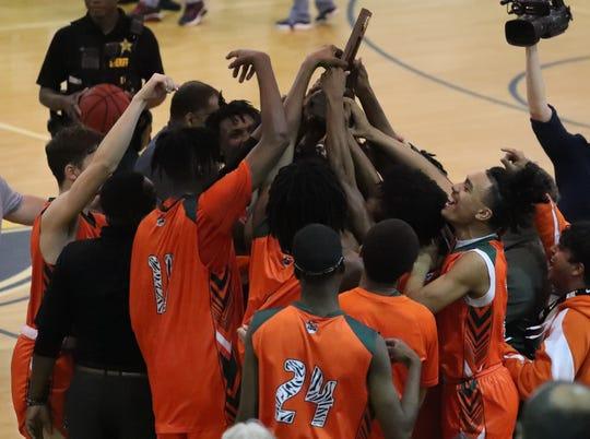 Dunbar celebrates with their district trophy. Dunbar beat Lehigh 68-64 in their boys basketball District 6A-12 championship game at Lehigh.