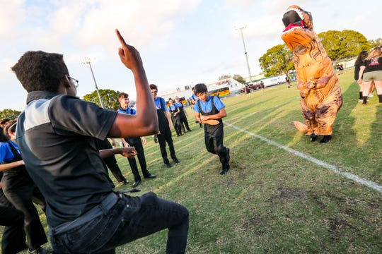 Raymond Kateregga, of Bishop Verot High School, and Joaquin Sibug, of Cape Coral, dance with band members. Parade participants met at Fort Myers High School to line up for the  Edison Festival of Light Grand Parade on Saturday, Feb. 15, 2020.