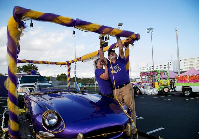 Kathryn Summers-Grider, left, helps her father, Dan Summers, add lights to their Alzheimer's Awareness float before the start of the 2020 Edison Festival of Light Grand Parade on Saturday, Feb. 15, 2020. They made the float to honor Dan's late wife, Joan. Their charity, Lady Friend, supports caregivers.