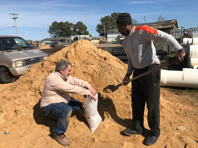 Lyle Skelton, 58, of Cleveland, hold open a bag while Rod Simmons, 46, of Jackson, shovels sand as they prepare for rising floodwaters on Feb. 15., 2020.