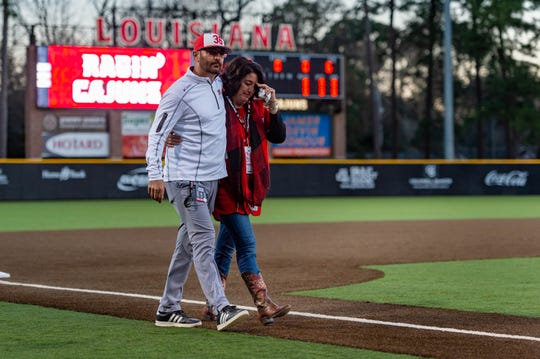 Ragin' Cajuns associate head coach Anthony Babineaux escorts Colleen Robichaux, late UL coach's Tony Robichaux's widow, onto the field at The Tigue before Friday's Opening Night loss to Southeastern Louisiana.
