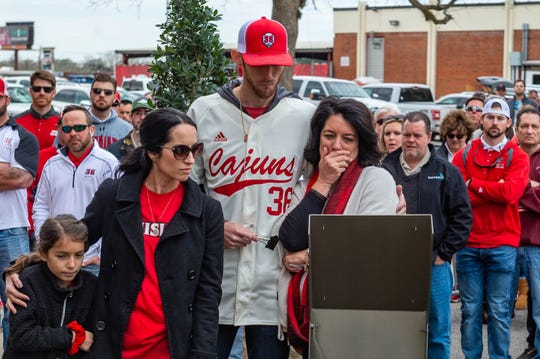 Colleen Robichaux (left), widow of Tony Robichaux, reads a plaque in front of the statue honoring the late Ragin' Cajuns coach along with son Austin and daughter Ashley.