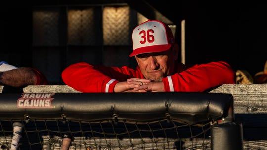 "Cajuns baseball coach Matt Deggs, wearing a ""36"" cap in honor of his predecessor Tony Robichaux, is shown in the dugout for the Cajuns' 2020 season opener against Southeastern Louisiana."
