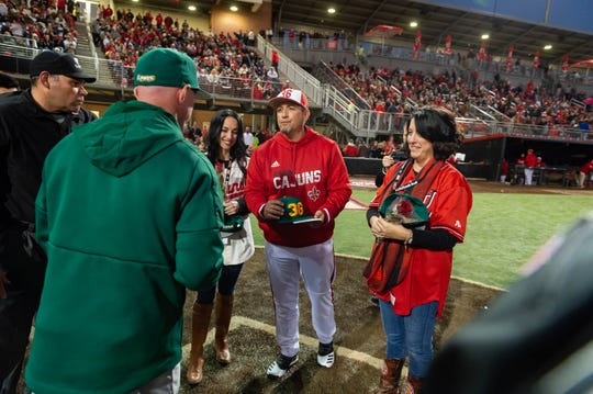 New UL coach Matt Deggs and Colleen Robichaux (right), late Ragin' Cajuns coach Tony Robichaux's widow, come to home plate before Friday night's game.