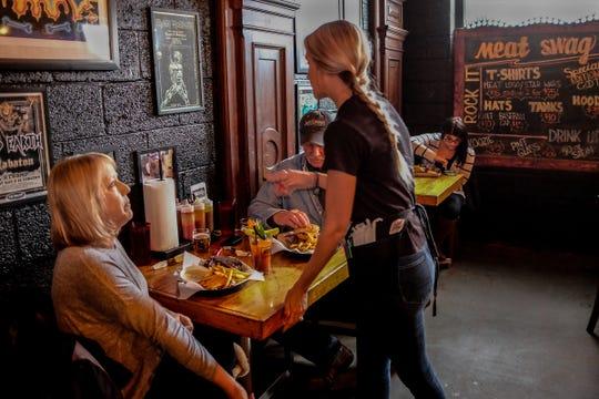 Olivia Gorman serves Ann Dittenber and Scott Miner lunch at Meat in Lansing's Old Town Thursday, Feb. 13, 2020.