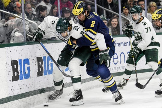 Michigan State's Jagger Joshua, left, and Michigan's Luke Martin go after the puck during the second period on Friday, Feb. 14, 2020, at the Munn Ice Arena in East Lansing.