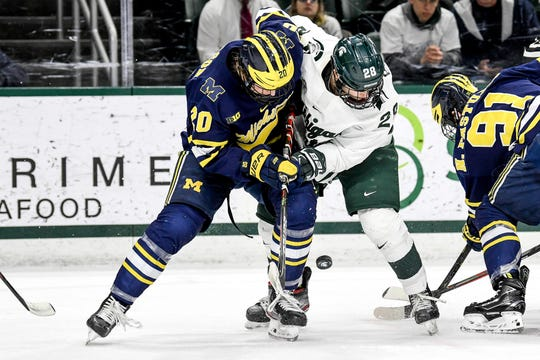 Michigan State's Gianluca Esteves, right, and Michigan's Keaton Pehrson battle for the puck during their game Friday at Munn Arena in East Lansing.