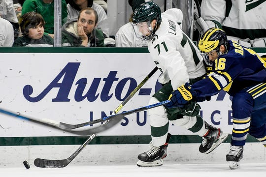 Michigan State's Logan Lambdin moves with the puck as Michigan's Jacob Hayhurst closes in during the second period on Friday, Feb. 14, 2020, at the Munn Ice Arena in East Lansing.