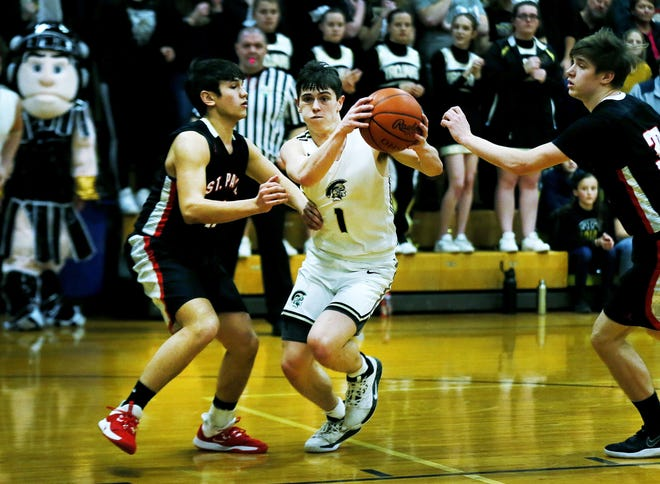 South Central High School's Simon Blair (1) drives to the basket as St. Paul High School's Adam Baker (10) guards Friday, February 14, 2020.