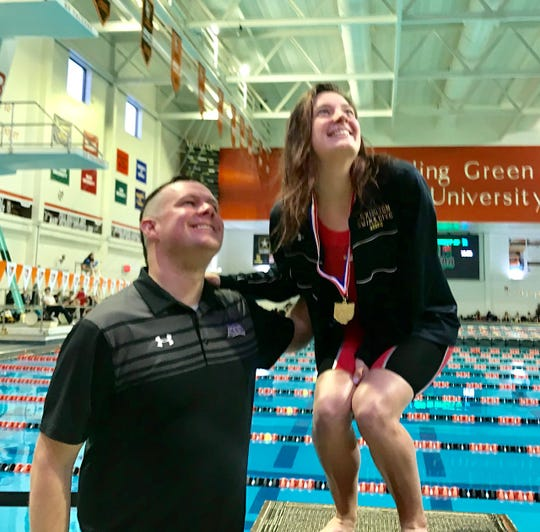 Lexington coach Brock Spurling and Lily Weeks pose for a picture taken from the balcony after Weeks won a district title in the 200 IM