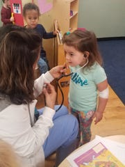 On-site nurse Monica Ramos delights an early learning (pre-school) student by letting her hear heartbeats.