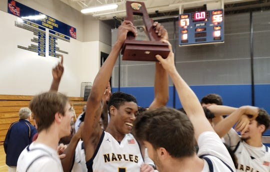 The Naples High School boys basketball team lifts the Class 5A-District 12 championship trophy after beating Barron Collier 67-56 at home on Friday, Feb. 14, 2020.