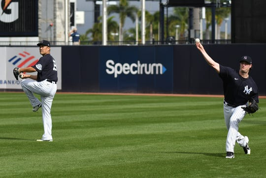 Feb 14, 2020; Tampa, Florida, USA; New York Yankees pitcher Masahiro Tanaka (left) and Gerrit Cole (right) throw during a spring training workout at George M. Steinbrenner Field.
