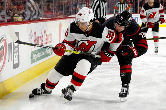 New Jersey Devils' Nicholas Merkley (39) battles with Carolina Hurricanes' Brock McGinn (23) during the third period of an NHL hockey game in Raleigh, N.C., Friday, Feb. 14, 2020.