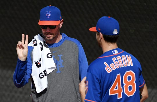 Feb 12, 2020; Port St. Lucie, Florida, USA; New York Mets pitching coach Jeremy Hefner (left) works with pitcher Jacob deGrom during the morning spring training workout.