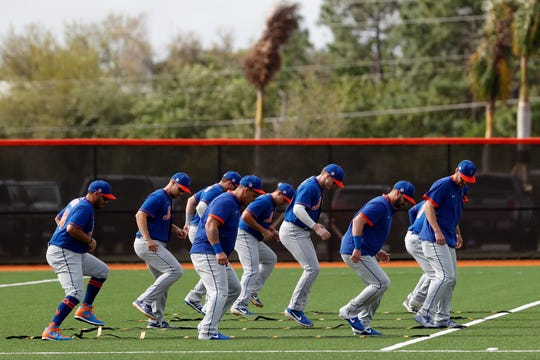 Members of the New York Mets warm up during spring training baseball practice Saturday, Feb. 15, 2020, in Port St. Lucie, Fla.