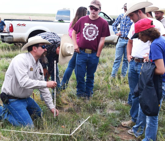 Nick Ashcroft, NMSU Extension range management specialist, demonstrates how to survey range grass availability during the New Mexico Youth Ranch Camp at CS Cattle Company ranch near Cimarron.