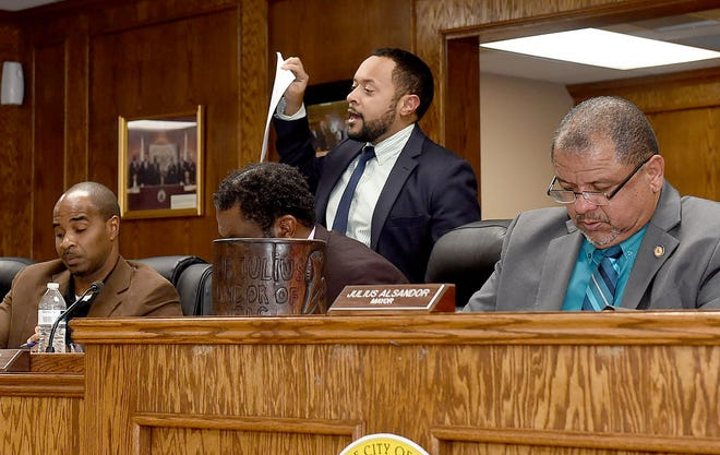 Opelousas City Attorney Travis Broussard speaks to the Board of Aldermen, as Mayor Julius Alsandor, in foreground, listens.
