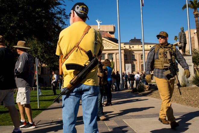 People walk near the State Capitol building with rifles on their backs as more than 2,500 people attend the Second Amendment Rally sponsored by  RidersUSA, AZFirearms & Gun Freedom Radio on Feb. 15, 2020, on the Senate Lawn of the Arizona State Capitol.