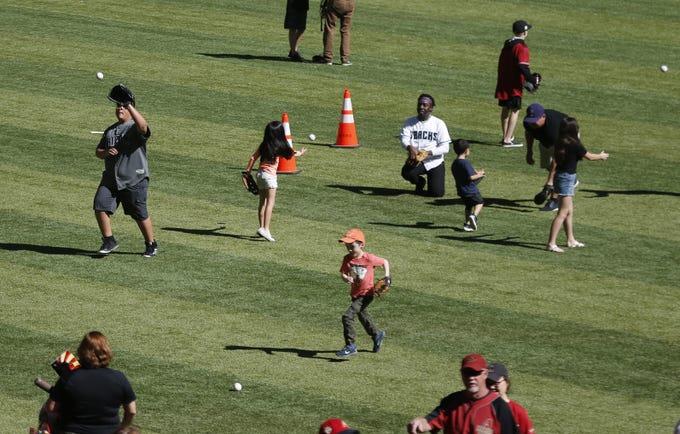 Fans throw baseballs during Diamondbacks Fan Fest at Chase Field in Phoenix on Feb. 15, 2020.
