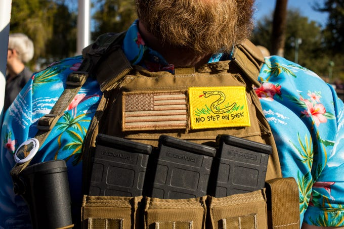 A man shows a patch playing on the Gadsden flag as more than 2,500 people attend the Second Amendment Rally sponsored by  RidersUSA, AZFirearms & Gun Freedom Radio on Feb. 15, 2020, on the Senate Lawn of the Arizona State Capitol.