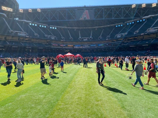 Thousands of D-backs fans soak up the sun in the outfield at Chase Field Saturday at the organizations 2020 Fan Fest.