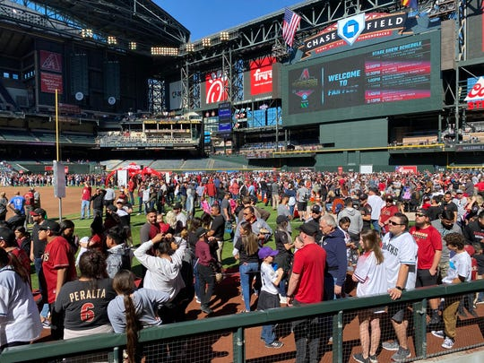 Spectators mingle near the visiting dugout at Chase Field Saturday at the Arizona Diamondbacks 2020 Fan Fest.