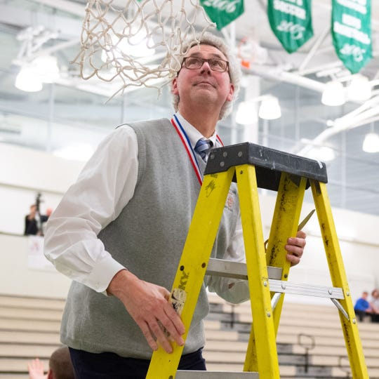 Dallastown Head Coach Jay Rexroth climbs the ladder to cut the net down after the YAIAA girls title game between Dallastown and Gettysburg in the Charles Wolf Gym at York College, Friday, February 14, 2020. The Wildcats defeated the Warriors 42-38.