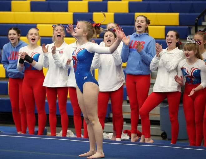 Members of the Lincoln gymnastics team cheer as teammate Eva Knudtson performs her floor exercise during Friday's class AA team competition at the South Dakota State Gymnastics meet at the Golden Eagles Arena in Aberdeen.