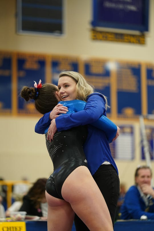 O'Gorman coach Skye Bork embraces one of her gymnasts during the Class AA team competition Friday in Aberdeen.