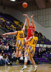 Yankton's Cooper Cornemann makes a three-point shot over Watertown's Kale Stevenson and Mason Morris on Friday, Feb. 14, at the Watertown Civic Arena.