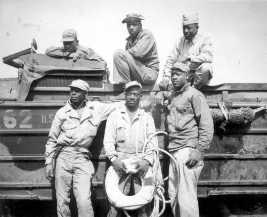 Seeking to rescue a Marine who was drowning in the surf at Iwo Jima, this sextet of Negro soldiers narrowly missed death themselves when their amphibian truck was swamped by heavy seas. From left to right, back row, they are T/5 L. C. Carter, Jr., Private John Bonner, Jr., Staff Sergeant Charles R. Johnson. Standing, from left to right, are T/5 A. B. Randle, T/5 Homer H. Gaines, and Private Willie Tellie.