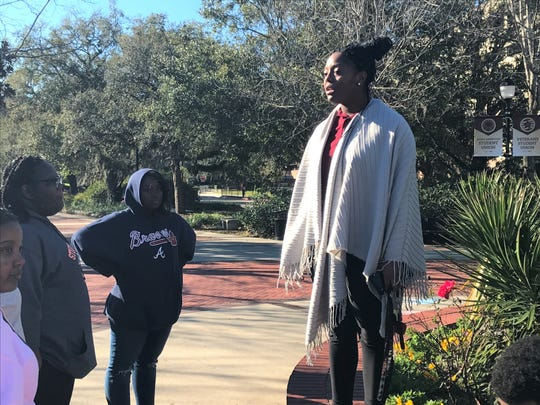 Florida State student Beatrice Davis speaks to students from Westlake High School in Atlanta on a college tour on the impact of Fred Flowers in front of his statue on campus.