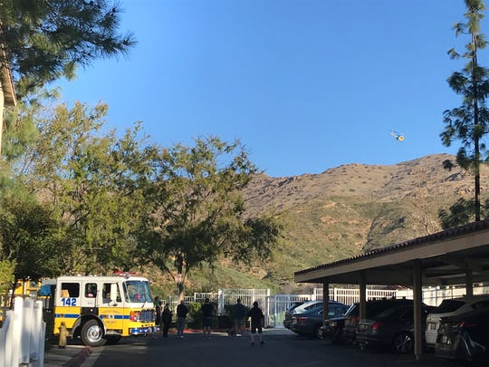Residents of the Shadow Ridge condominium complex in Oak Park watch a helicopter circle over hills above Oak Bend Lane Saturday morning as an injured hiker was rescued from a nearby trail.