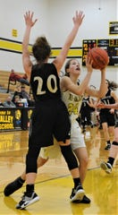 Tri-Valley's Anna Krupa goes up for a shot against Carrollton's Lauren Mormo in Saturday's 65-25 victory in Division II sectional play.