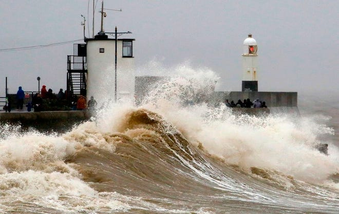 """Huge waves crash against the sea wall at Porthcawl, south Wales as Storm Dennis hits the country on February 15, 2020. As Storm Dennis sweeps in, the country is bracing itself for widespread weather disruption for the second weekend in a row. Experts have warned that conditions amount to a """"perfect storm"""", with hundreds of homes at risk of flooding."""